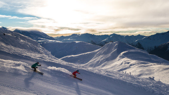 Two female skiers skiing off the top of the Harmony Chair into Whistler Mountain's iconic Burnt Stew Basin